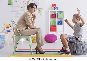 Angry young boy sitting on a pouf, talking with psychologist