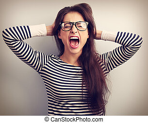 Angry young business woman in glasses strong screaming with...