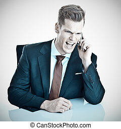 Angry young businessman screaming into his cellphone