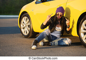 Angry young fashion hipster woman sitting next to her car
