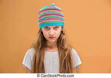 Angry young girl in hat looking at camera with hate
