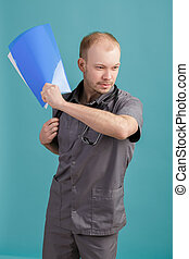 angry young male doctor holding a folder with papers on blue background