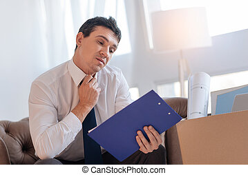 Angry young man sitting with a blue clipboard after losing his job