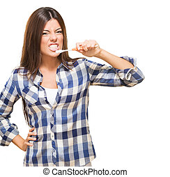 Angry Young Woman Brushing Her Teeth against a white...
