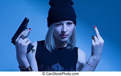 Angry young woman with a gun making obscene finger gesture