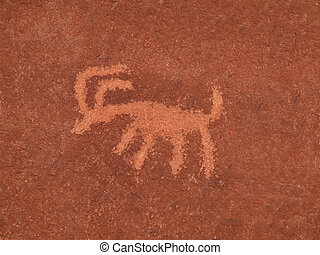 Ancient American Indian petroglyph on a red sandstone wall.