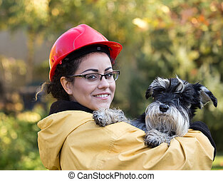 Animal rescue team - Young woman in raincoat and with helmet...