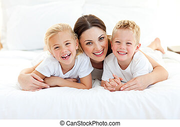 Animated children and their mom having fun lying on a bed at home