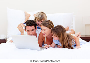 Animated family buying online lying down on bed at home