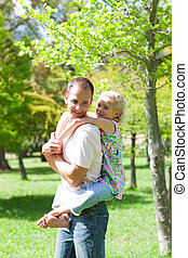 Animated father giving his daughter piggy-back ride in a park