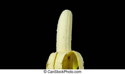 Back and forth video of a half peeled banana moving on black background