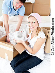Animated young couple packing a box