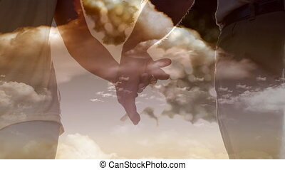 Animation of a Christian cross over a couple holding hands...