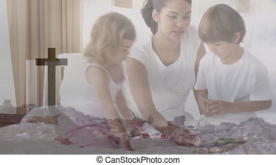 Animation of a Christian cross over a family playing ...