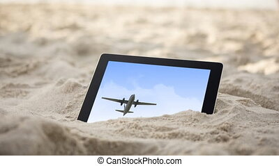 Animation of a digital tablet in sand with an airplane flying on the screen