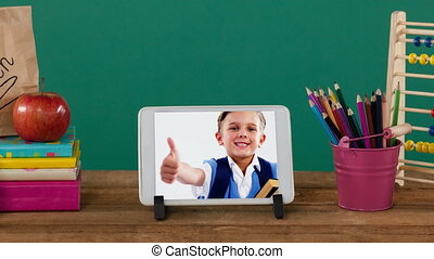 Animation of a digital tablet showing Caucasian boy giving thumbs up on the screen