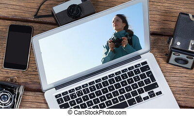 Animation of a laptop showing Caucasian woman on the screen
