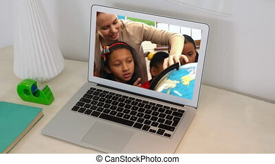 Animation of a laptop showing multi-ethnic group of children...