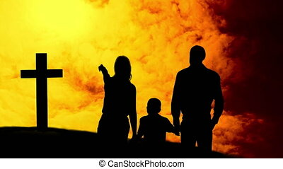 Animation of a silhouettes of Christian cross and a family ...