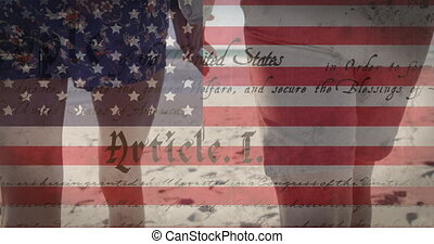 Animation of American flag waving and constitution text over mixed race couple by seaside on summer holiday holding hands in the background. American society diversity concept digital composition.