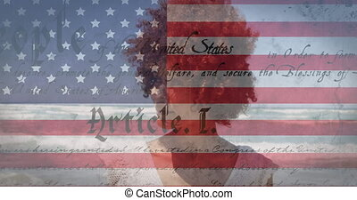 Animation of American flag waving and constitution text over mixed race woman by seaside on summer holiday in the background. American society diversity concept digital composition.
