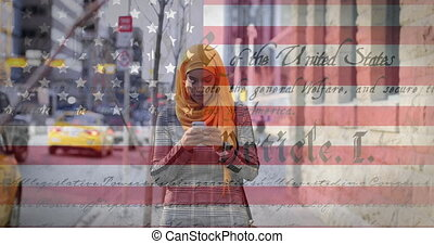 Animation of American flag waving and constitution text over mixed race woman in hijab using smartphone in the background. American society diversity concept digital composition.
