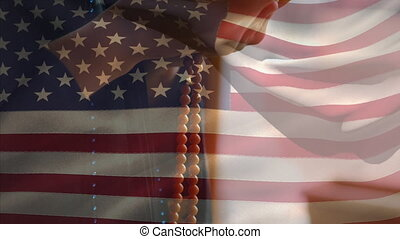 Animation of American flag waving over hands of mixed race ...