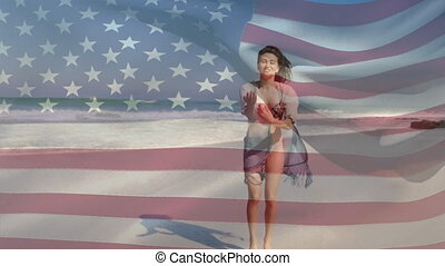 Animation of American flag waving over happy woman jumping dancing on beach by seaside on summer holiday in the background. American society diversity concept digital composition.