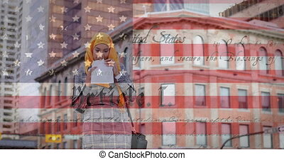 Animation of American flag waving over mixed race woman in hijab eating takeaway sandwich in city street in the background. American society diversity concept digital composition.