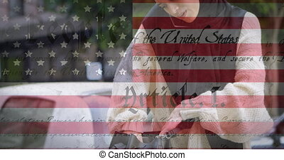 Animation of American flag waving over mixed race woman in hijab talking on her smartphone in the background. American society diversity concept digital composition.