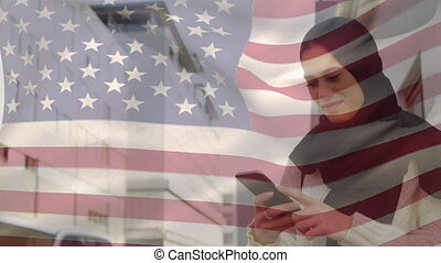 Animation of American flag waving over mixed race woman in hijab using smartphone in the background. American society diversity concept digital composition.