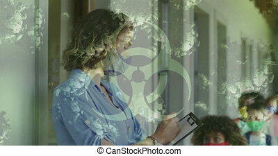 Animation of biohazard sign covid 19 cells and female teacher and schoolchildren in face masks. Healthcare and protection during coronavirus covid 19 pandemic, digitally generated video.