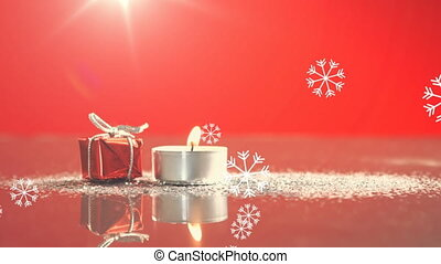 Animation of candle and present, snow falling on red background