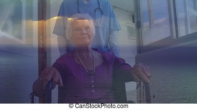 Animation of caucasian senior woman on wheelchair and medic over seascape. senior health and lifestyle in social welfare home.
