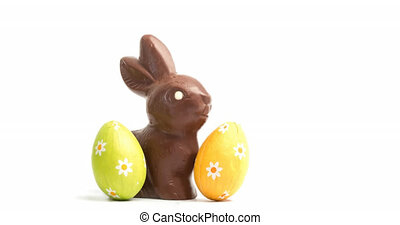 Animation of chocolate easter bunny and eggs on white background