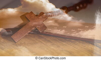 Animation of Christian cross over rosary beads, clouds with wooden surface in the background. Easter religion faith concept digitally generated image.