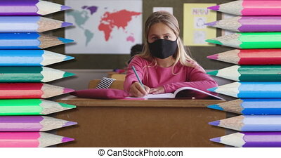 Animation of colourful crayons over girl wearing face mask sitting in classroom writing. education and learning concept digitally generated video.
