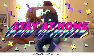 Animation of colourful text Stay At Home over Caucasian couple sitting on a couch