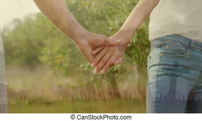 Animation of couple holding hands standing in green field in countryside over silhouettes of three C