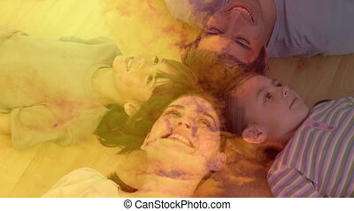 Animation of couple with son and daughter lying on the floor, smiling with orange clouds.
