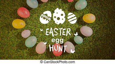 Animation of easter egg hunt text with multi coloured easter eggs in grass. easter tradition and celebration concept digitally generated video.