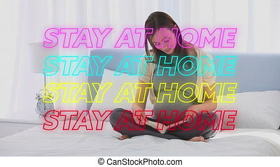 Animation of four lines of colourful neon words Stay At Home over pregnant Caucasian woman reading b