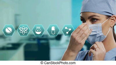 Animation of hexagon medical icons over female doctor wearing face mask. global covid 19 pandemic and digital interface concept digitally generated video.