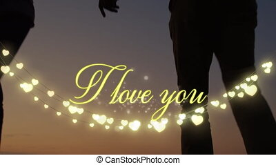 Animation of I Love You text written with string of fairy lights and couple in love by the sea in summer holding hands running in the background. Valentines Day celebration concept digital composite.