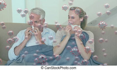Animation of macro Covid-19 cells floating over Caucasian couple sitting on a couch sneezing into ti