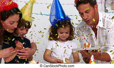 Animation of multi coloured confetti falling over family in party hats. birthday party celebration festivity concept digitally generated image.