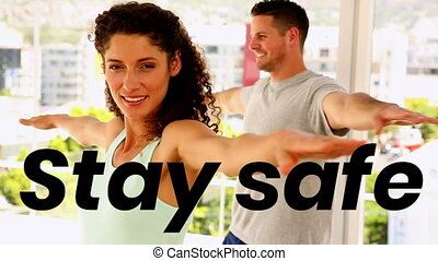 Animation of stay safe text over woman and man practicing yoga at home. coronavirus covid 19 global pandemic health crisis concept digital composite.