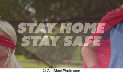 Animation of text Stay Home Stay Safe over Caucasian boy wearing a cape
