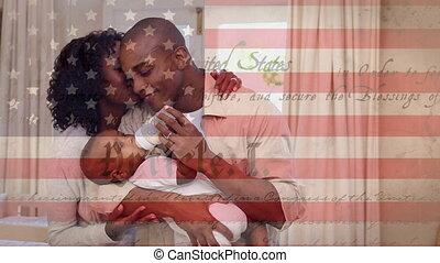Animation of U.S. constitution floating with U.S. flag over mixed race couple feeding a baby. United States of America presidential election democracy holiday concept digital composition