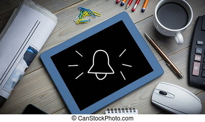 Animation of white bell icon flickering on screen of a digital tablet put on a desk with a cup of co